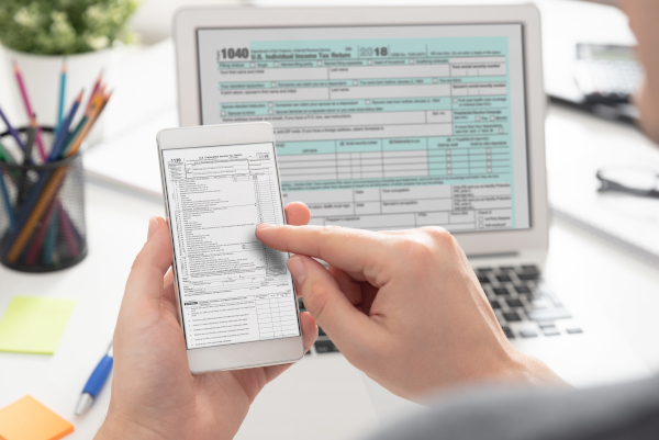 Man-filling-tax-information-using-mobile-devices-1128634340_5691x3800.